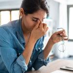 Mulher estressada no trabalho pensando nas técnicas para combater o estresse