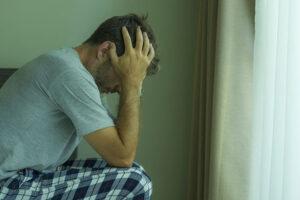 homem sentado na cama com as mãos na cabeça e com sintomas de síndrome do pânico