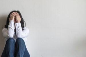 Uma mulher sozinha, com sentimento de solidão, um dos sintomas da depressão. Identifique outros!